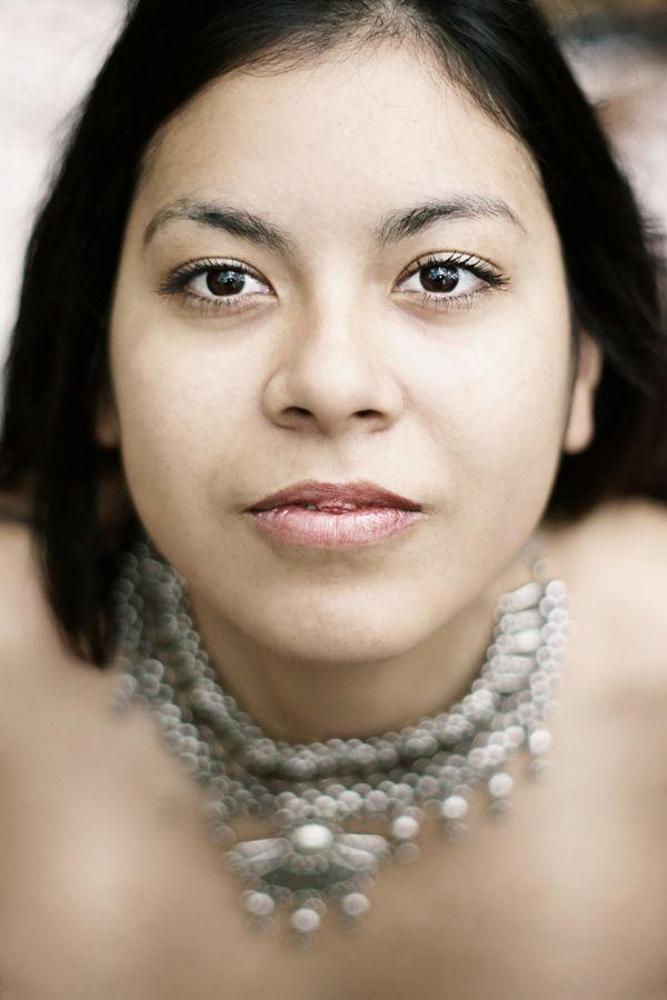 Portrait d'Ana en contre-plongée à Grézieu la Varenne. Pour ce portrait très serré, Ana porte un collier métallique et regarde intensément l'objectif.