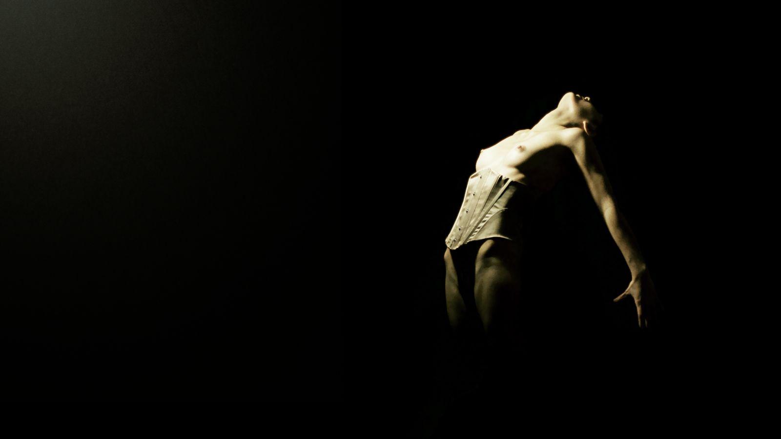Le corps presque nu de Maeva en serre-taille semble irrésistiblement attiré vers une présence à la fois sombre et lumineuse. Photo en studio à Caluire.