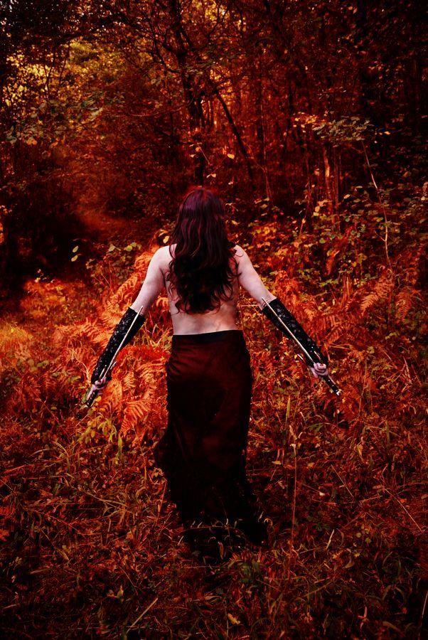 Bohème manie les saïs pour une sabre dance dans une forêt au couleurs incandescentes de l'automne. Est est torse nu et sa chevelure rousse recouvre son dos.