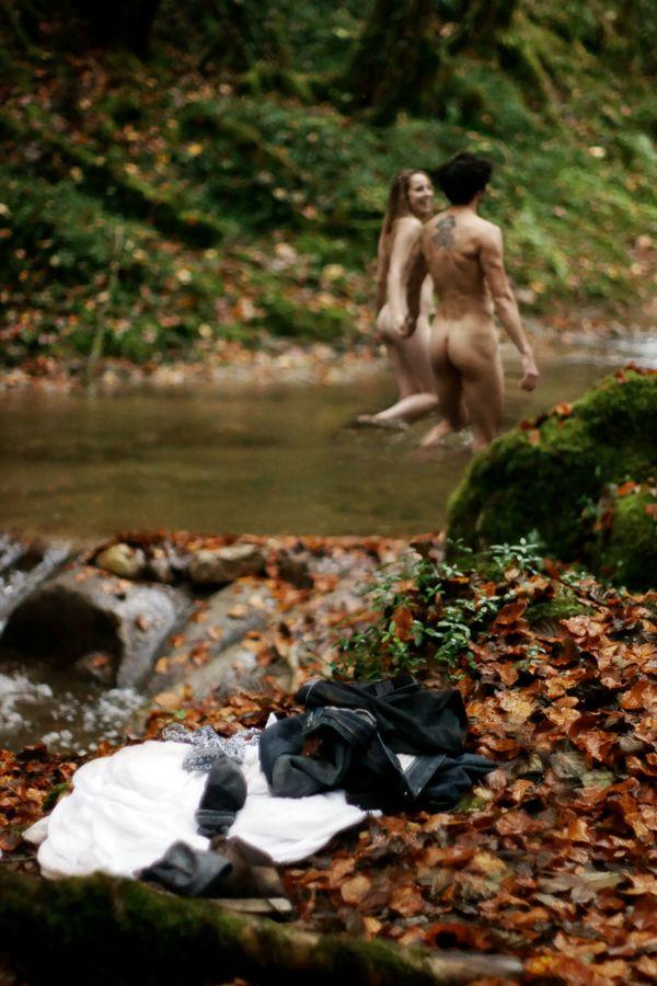 Au bord de la rivière, deux silhouettes, nues et joyeuses, s'éloignent en se tenant par la main dans un abandon total de leur vie antérieure.