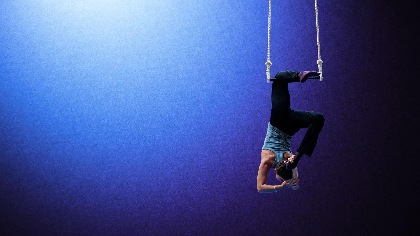 Diane est crochetée par le genou au trapèze d'Overground Circus à Lyon 5e. Elle vient, en souplesse arrière, toucher sa tête avec son pied.