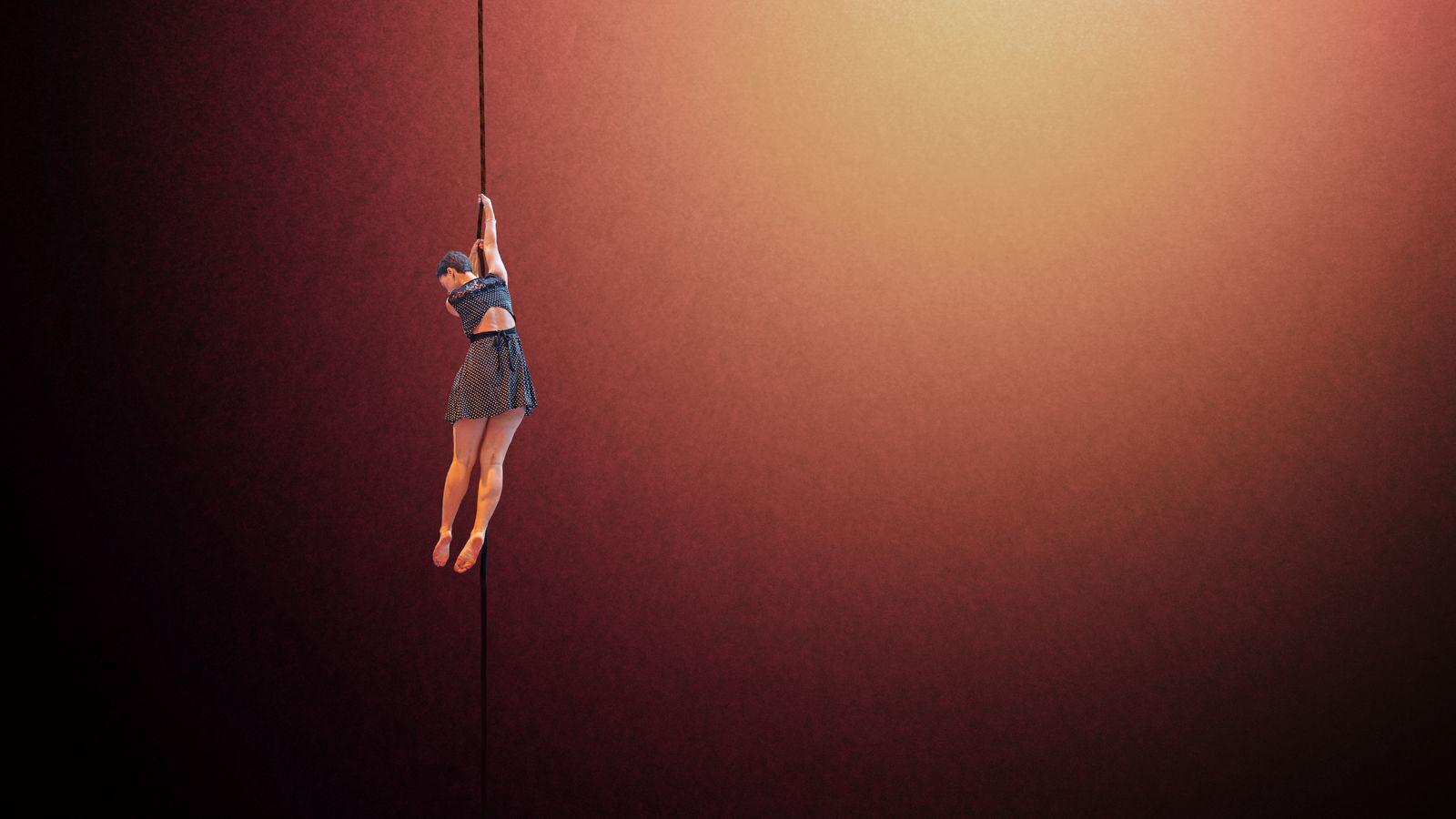 Diane est suspendue à la corde lisse du gymnase d'Overground-circus à Lyon 5e. Elle pratique l'aérien en robe noire à pois blanc avec un dos-du.