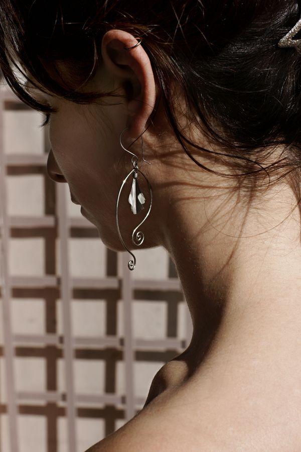 Mathilde, de trois quart dos, porte une boucle d'oreille ornée d'une plume noire et blanche. La plume est encadré de boucle argentée.