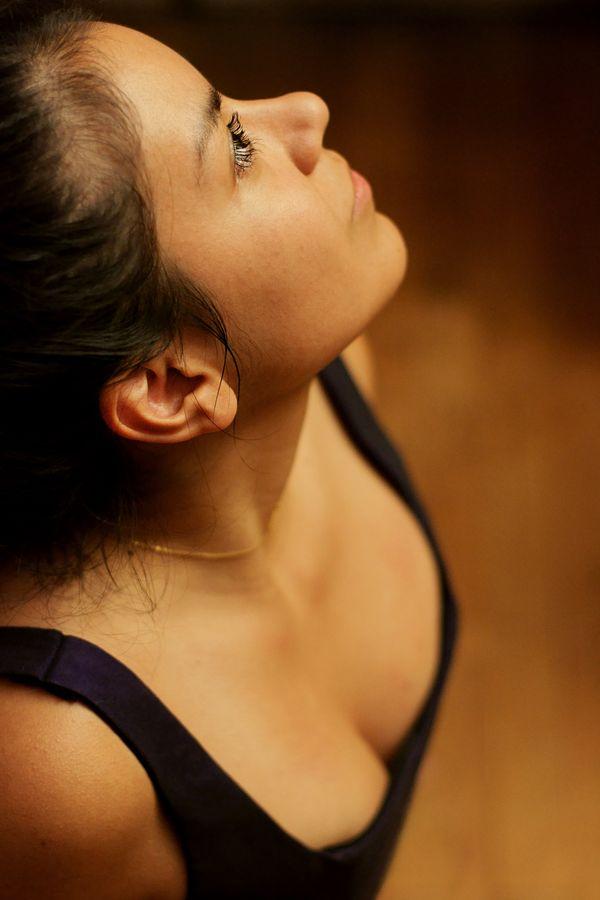 Portrait de profil d'Ana en corset violet. Elle lève son regard orné de longs cils vers la lumière et esquisse un léger sourire énigmatique.