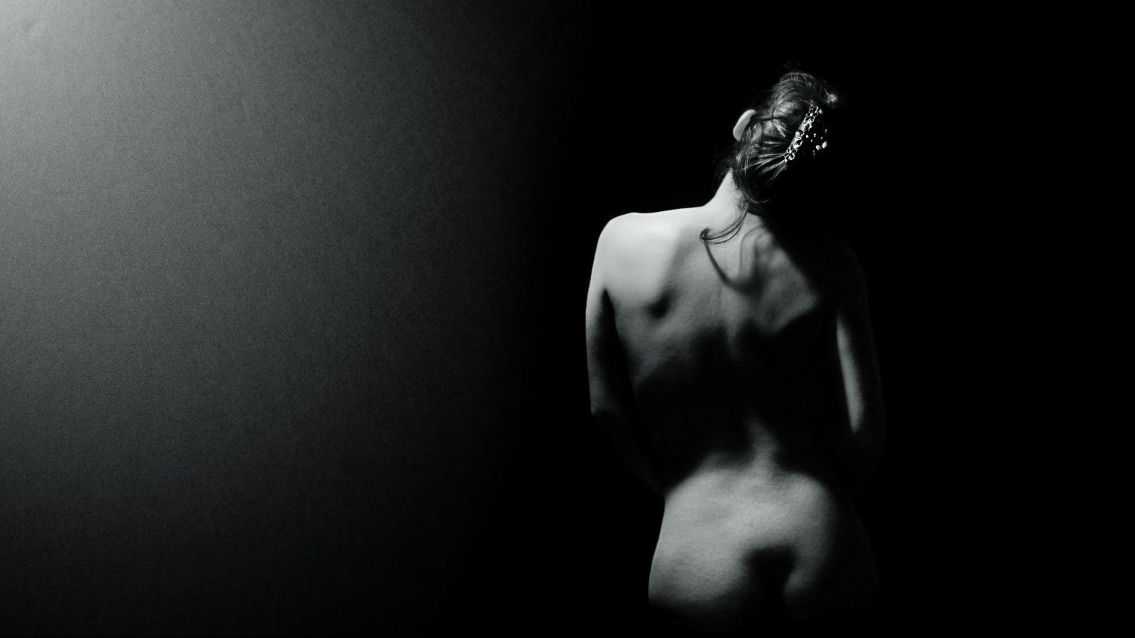 Un halo de lumière douce éclaire le dos nu de Maeva. Sur son corps, en noir et blanc, les ombres et une boucle de cheveux dessinent de jolies courbes.