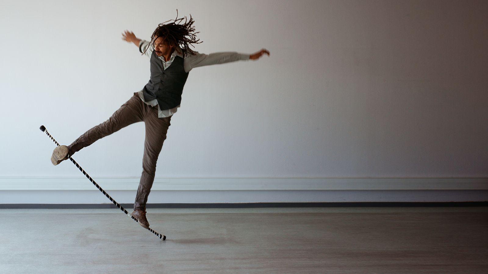 Jean-Souleymane fait du surf sur son acrostaff dans la cuisine d'une ancienne école de danse à Villeurbanne. Le staff se courbe sous le poids de l'acrobate.