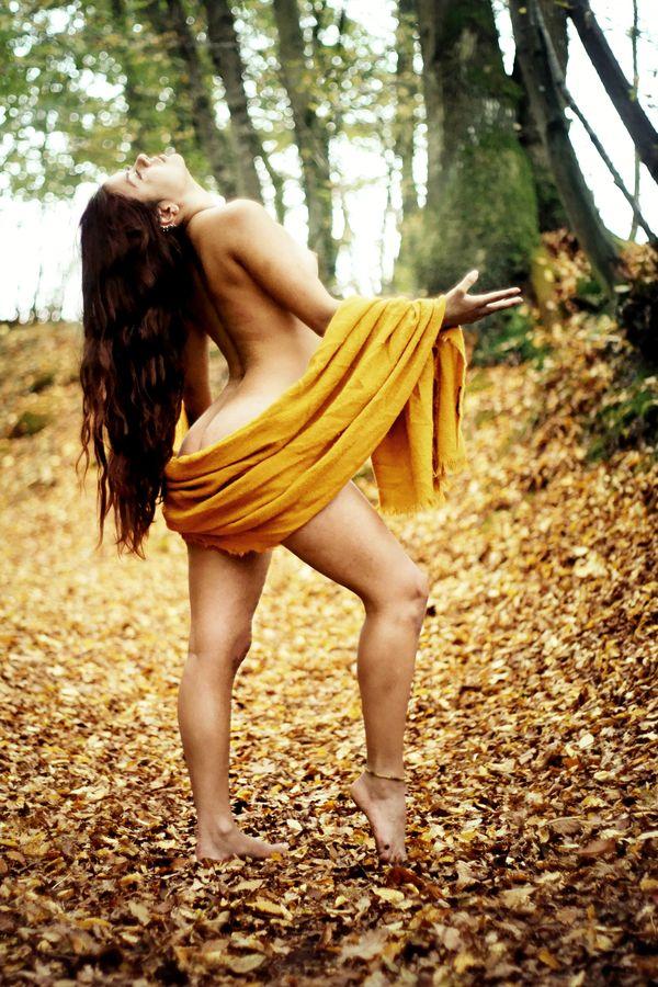 En automne, Ana s'abandonne à la nature qui vient remplir son corps d'énergie. Elle est seulement vêtue d'un paréo jaune et de sa longue chevelure brune.