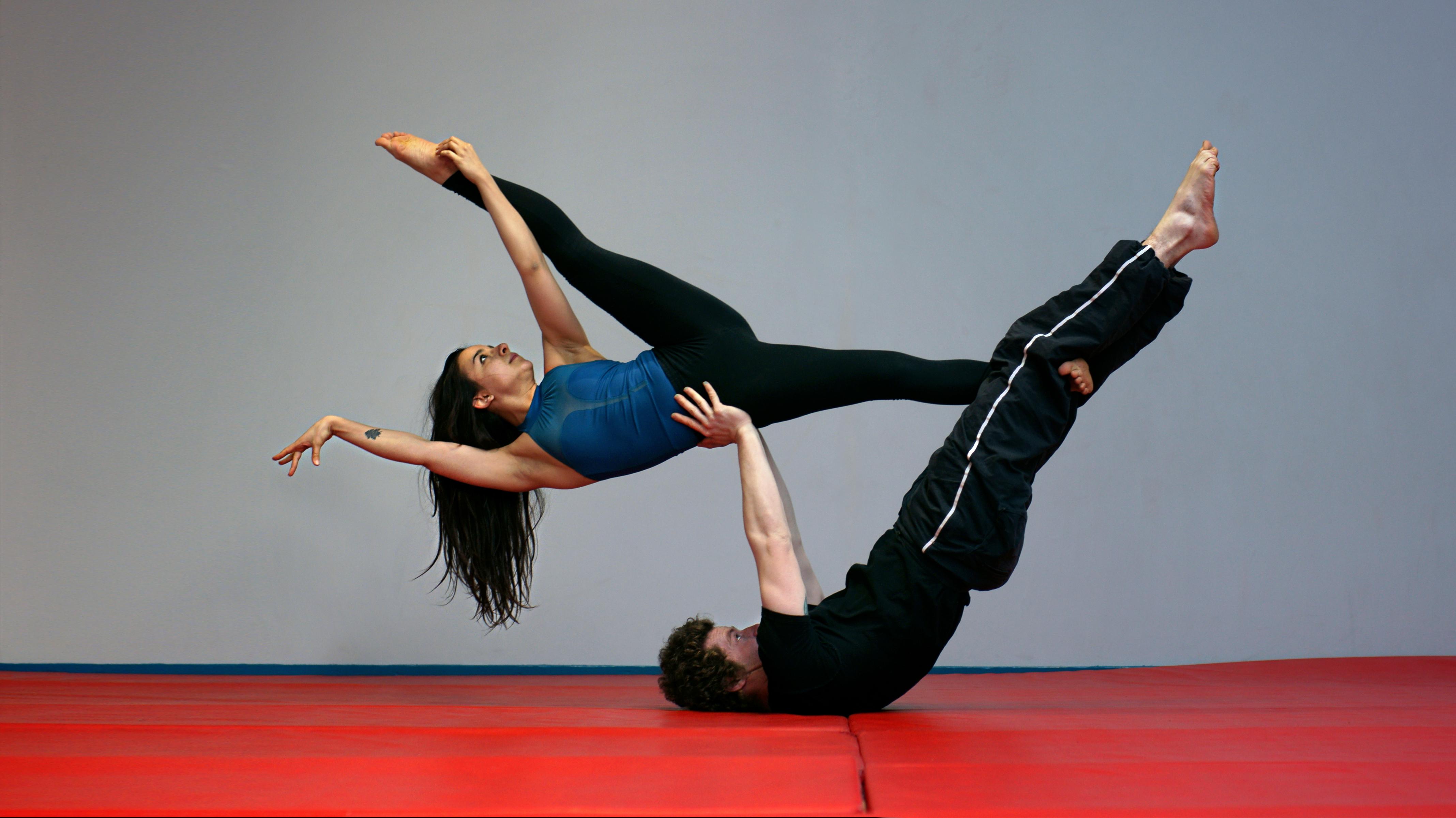 Iona et Jonas font un Y counterbalance, une figure d'AcroYoga. La longue chevelure brune de Iona pend au dessus du tapis d'Overground Circus, à Lyon 5e