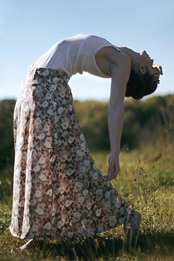 Mathilde en longue jupe à fleur, est courbée en arrière, avec le bras pendant pour une séance de danse contemporaine dans la nature de Saint-Laurent-d'Agny.