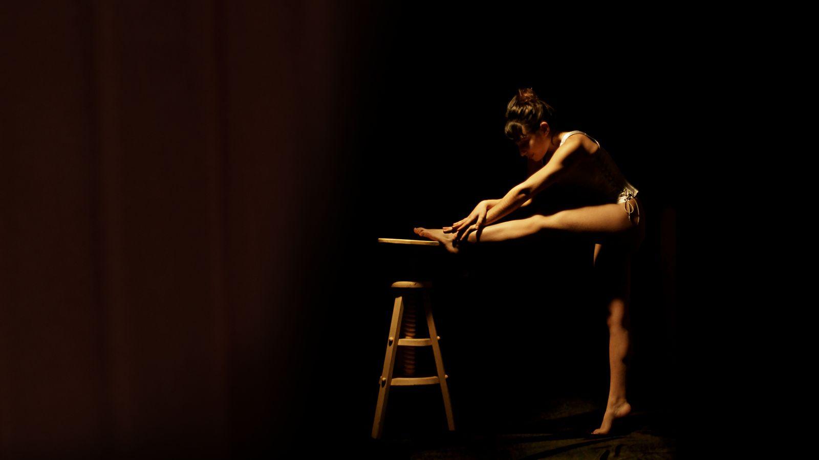 Maeva, en pleine préparation, s'étire en s'appuyant sur un tabouret haut. Derrière le rideau, on entend le public qui s'installe avant le spectacle.