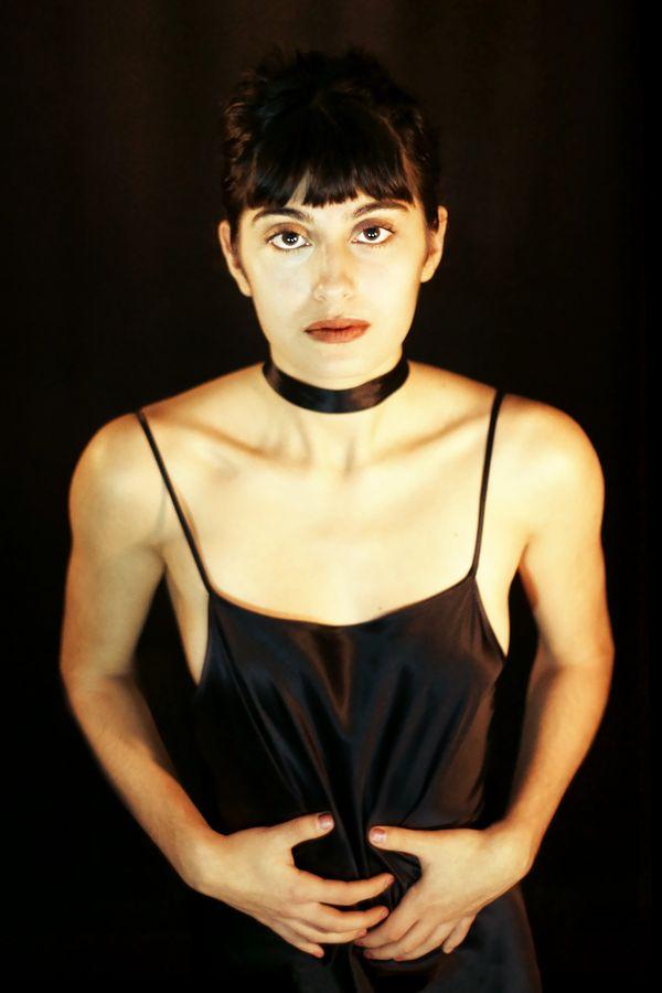 Maeva froisse son fourreau de satin noir en resserrant ses mains sur son ventre. On l'imagine dans un cabaret des années 20 en pleine période du Charleston.