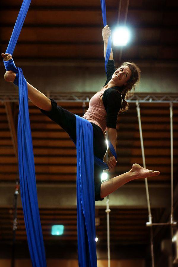 Céline, s'entraine au tissu aérien à l'École du Cirque San Priote. Alors qu'elle est suspendue à son agrès, elle arbore un magnifique sourire.