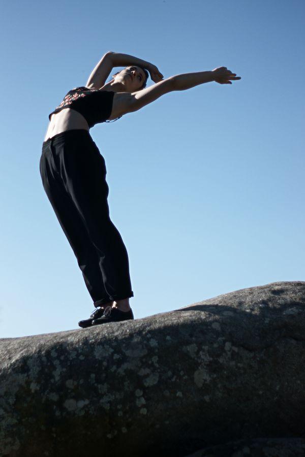 Sur un rocher à Saint-Laurent d'Agny, Mathilde fait de la danse contemporaine. Son corps est courbé comme s'il était attiré par le soleil couchant.