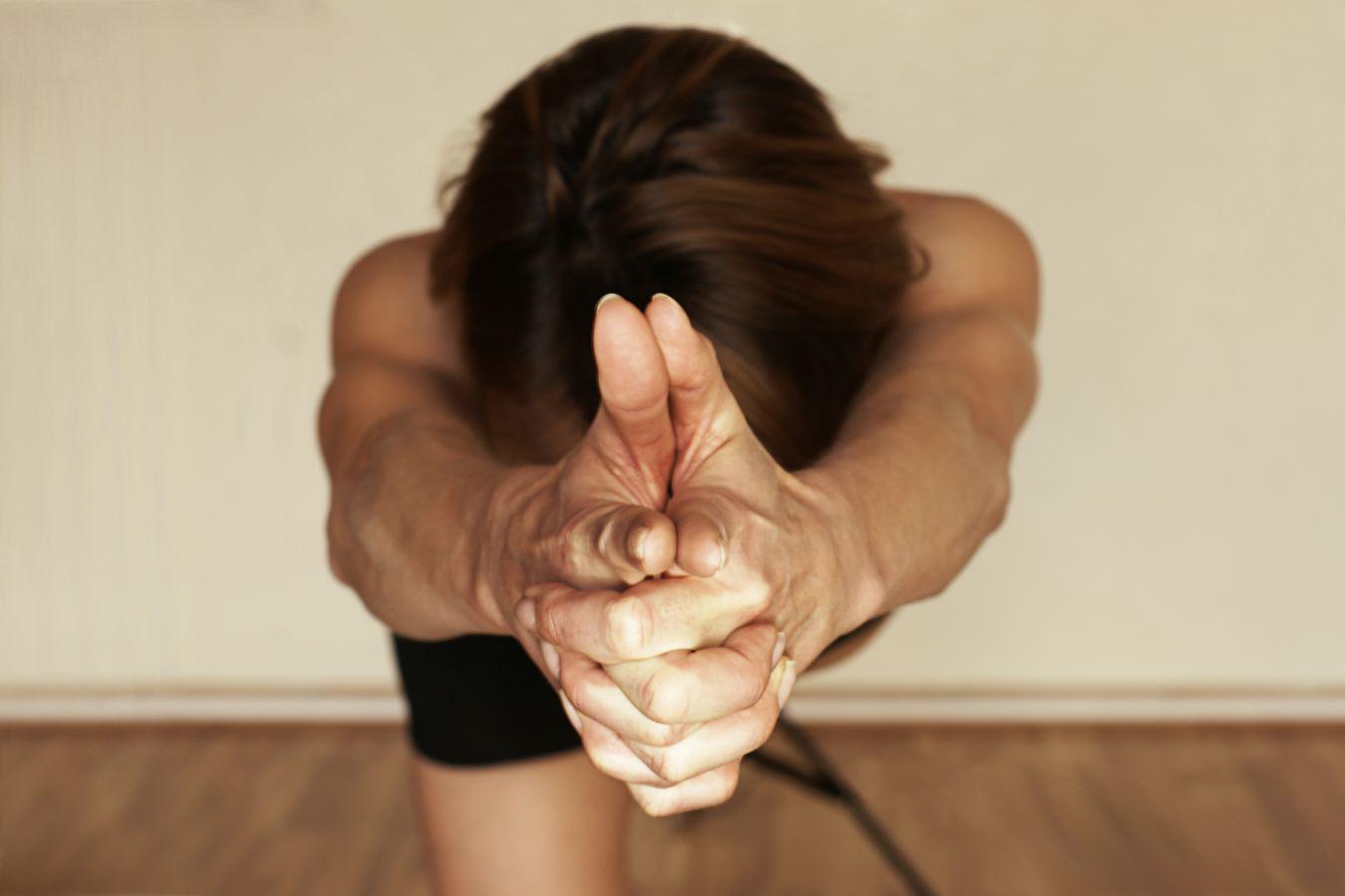 Au studio de yoga, Sydney Martinie pointe ses doigts vers l'objectif, alors que la yoguiste s'étire au maximum dans une pause appelée tuladandasana.