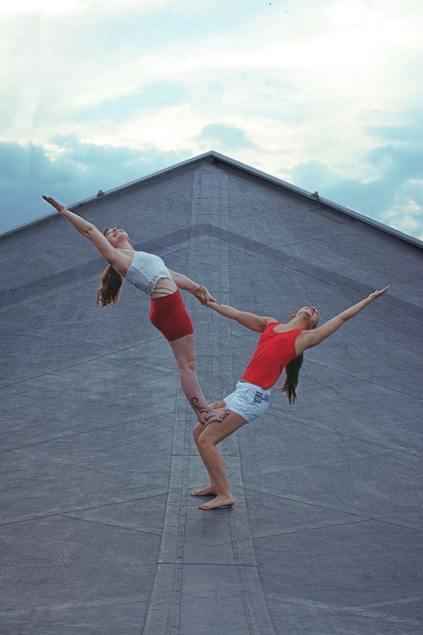 Iona porte Marine en drapeau sur le toit d'un amphithéâtre à la Doua. Cette figure s'appelle thightstand en acroyoga et flag en porté acrobatique.