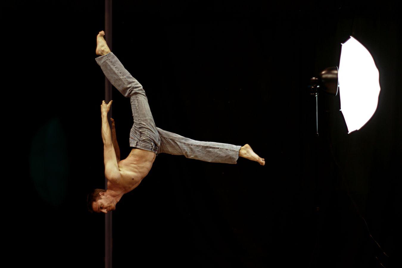 Joan fait du mat chinois à l'École de Cirque San Priote où il enseigne le cirque, jonglerie et acrobatie. il est éclairé par un parapluie de studio.
