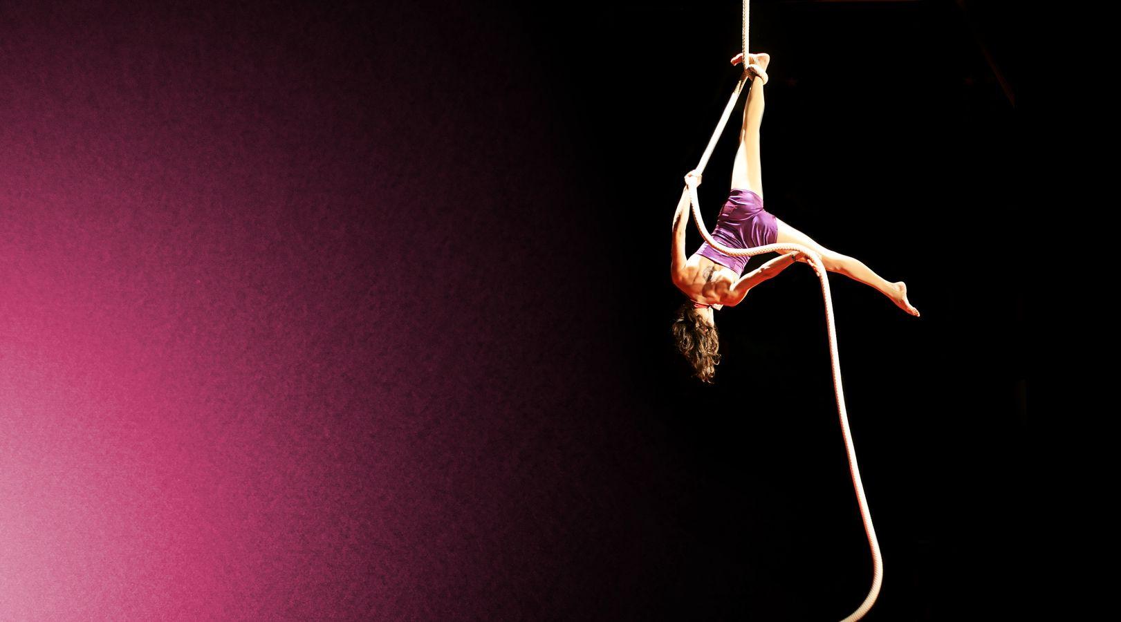 Caroline, suspendue de dos à sa corde lisse, répète son numéro sous le chapiteau du Karnaval Humanitaire. L'arrière-plan lui fait voir la vie en rose.