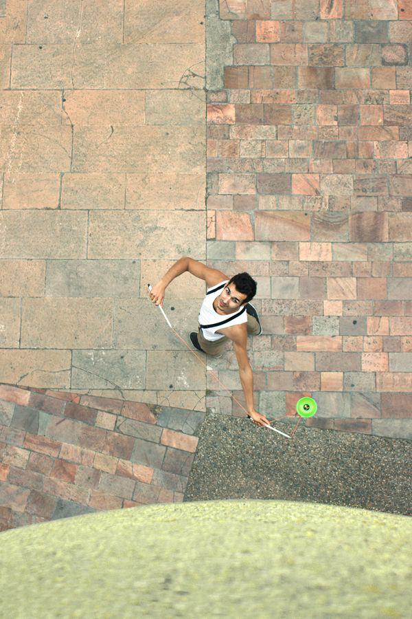 Yohan Durand, un diaboliste de l'AJIL est vu du dessus sur le parvis de l'Auditorium de Lyon. Il fait tourner son diabolo vert autour de lui en vertax.