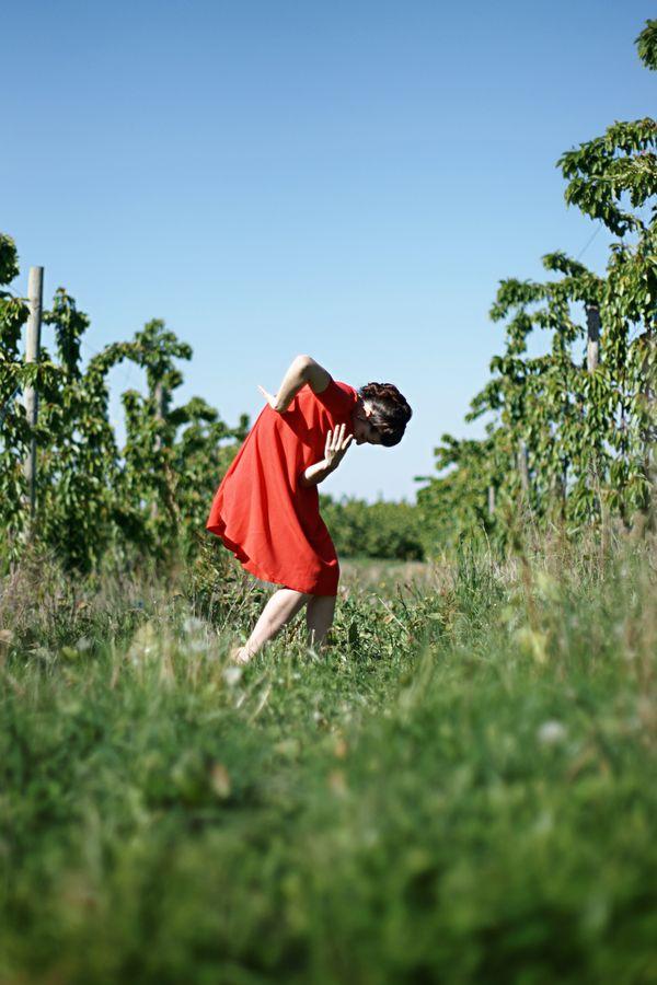 Mathilde fait de la danse contemporaine au milieu des cerisiers à Saint-Laurent-d'Agny. Sa robe rouge contraste avec le vert de la nature et le ciel bleu.