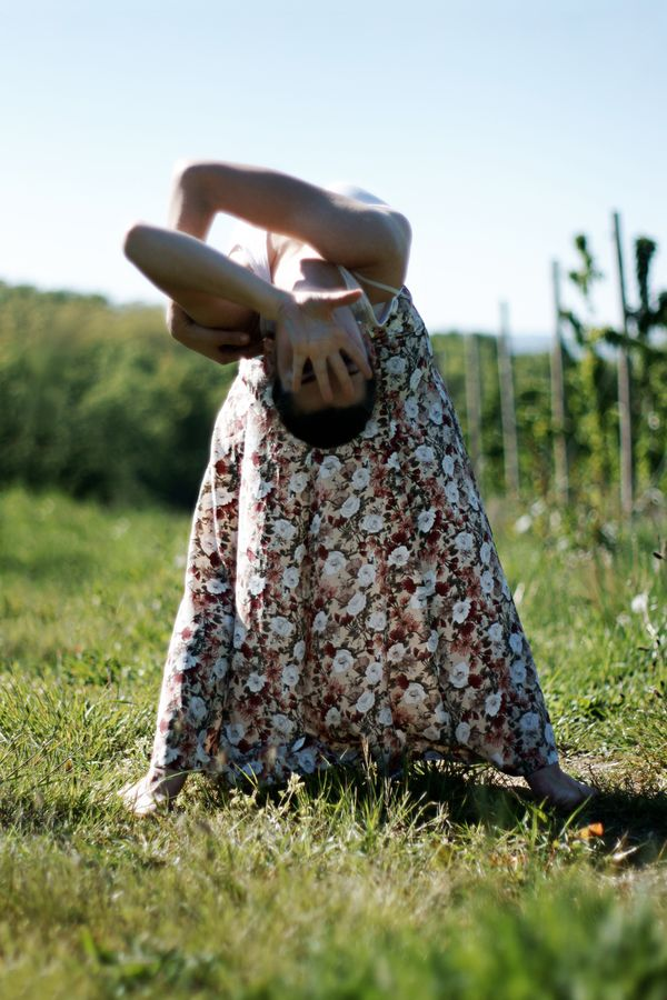 Mathilde en longue jupe à fleur, fait de la danse contemporaine à Saint-Laurent-d'Agny. Elle nous regarde à travers la main qui lui cache le visage.