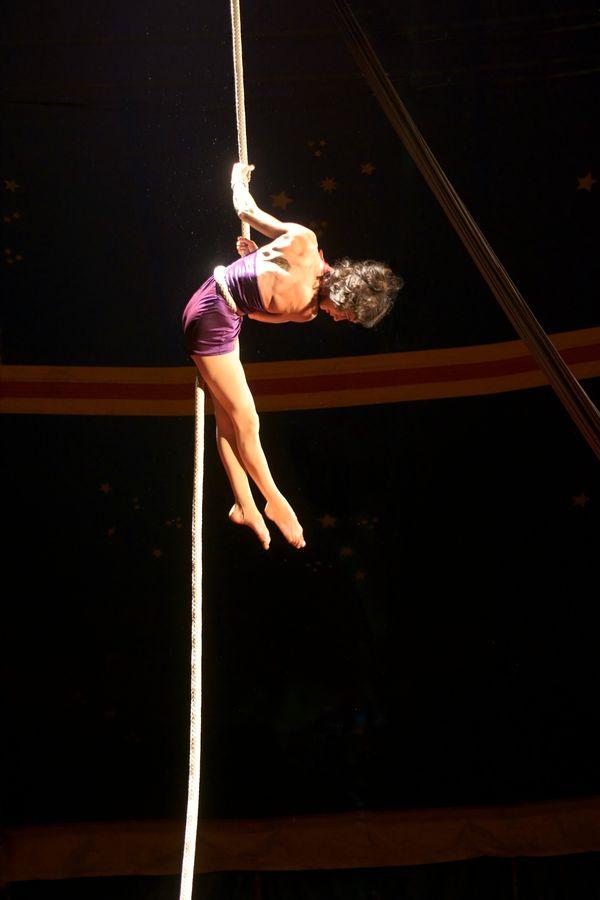 Caroline est suspendue à sa corde lisse sous le chapiteau du Karnaval Humanitaire. Son corps forme un angle, plus fermé que l'angle droit.