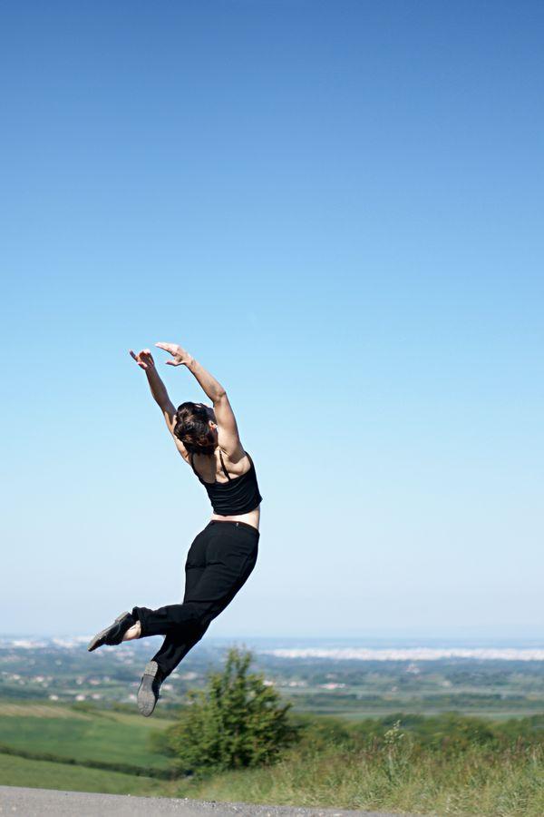 Mathilde saute au dessus de l'horizon pour une session de danse contemporaine, non loin de la chapelle de Saint-Laurent d'Agny.