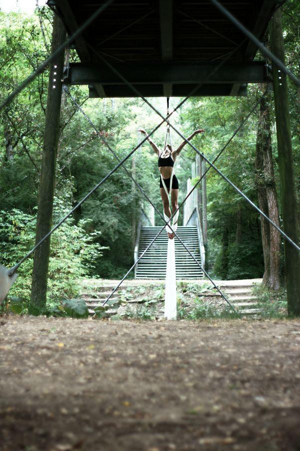 Sydney Martinie fait du tissu aérien sous la passerelle du parc de la Feyssine. Son corps s'inscrit dans le losange formé par les câbles du pont.