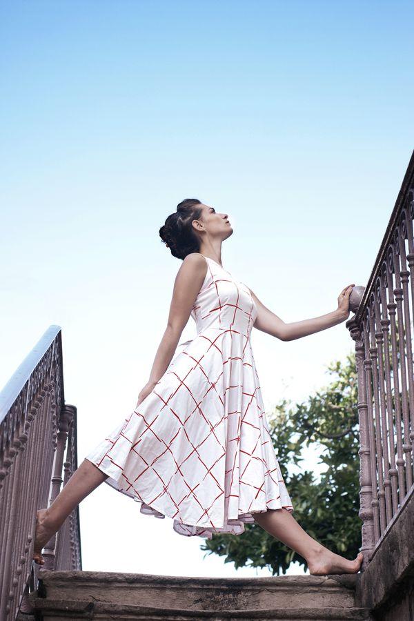 Mathilde en robe à carrés rouges fait de la danse contemporaine, rue Burdeau. Ses pieds sont aux coins d'un carré formé par l'escalier et les rambardes.