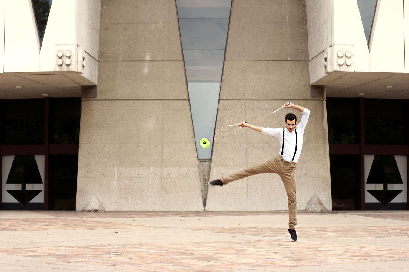 Yohan Durand fait du diabolo devant l'Auditorium de Lyon. Dans un mouvement très dansé, le jongleur propulse son agrès au centre de la scène.