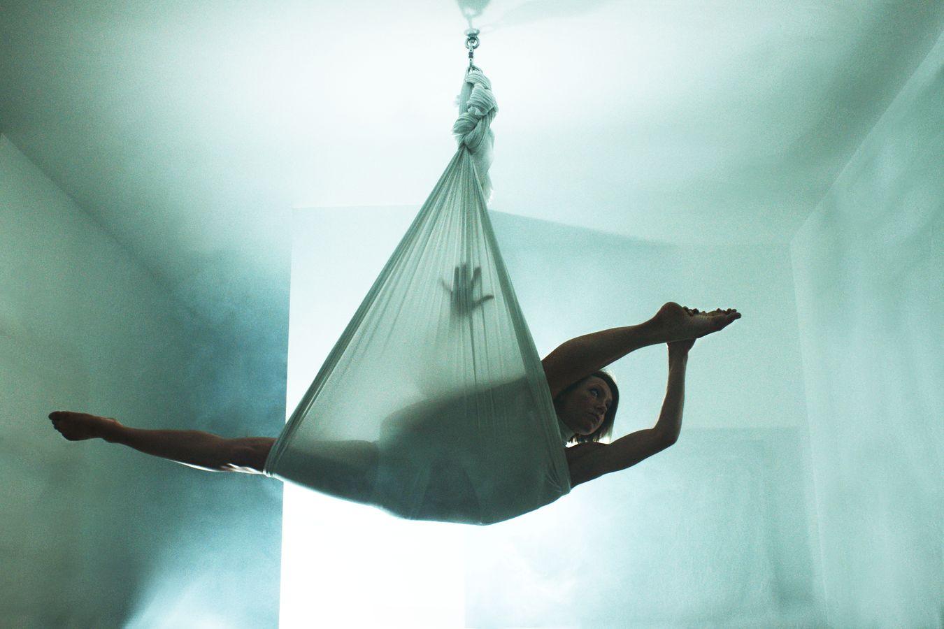 Dans un berceau aérien, Sydney Martinie fait du Yoga aérien. Alors qu'elle est en grand écart, on voit l'ombre de sa main à travers le tissu.