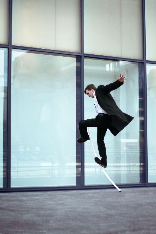 Étienne, compagnie Mimétis fait de l'AcroStaff, devant une baie vitrée. Pour cette acrobatie, le circassien porte des vêtements chics, chemise et redingote,