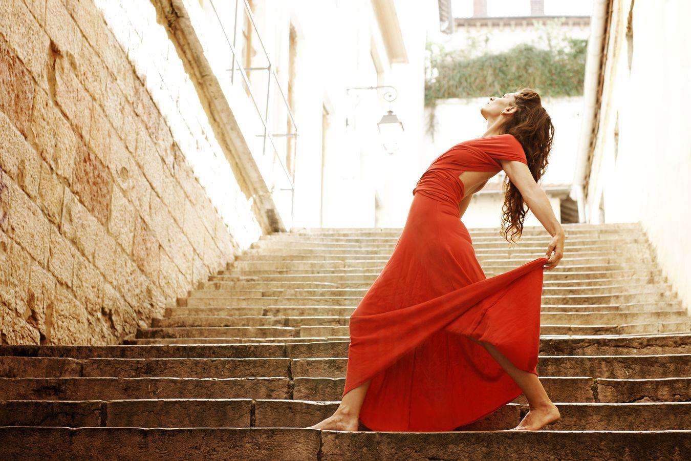 Mathilde fait de la danse contemporaine en robe rouge dans les escaliers du passage Thiaffait dans les pentes de la Croix-Rousse à Lyon.