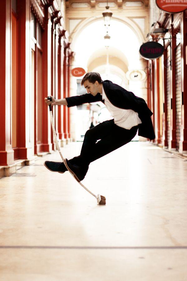 Étienne, de la compagnie Mimétis est en équilibre sur son AcroBroom en costume de ville dans le passage de l'Argue à Lyon. Sur cette image, nous pouvons remarquer la flexibilité du bâton.
