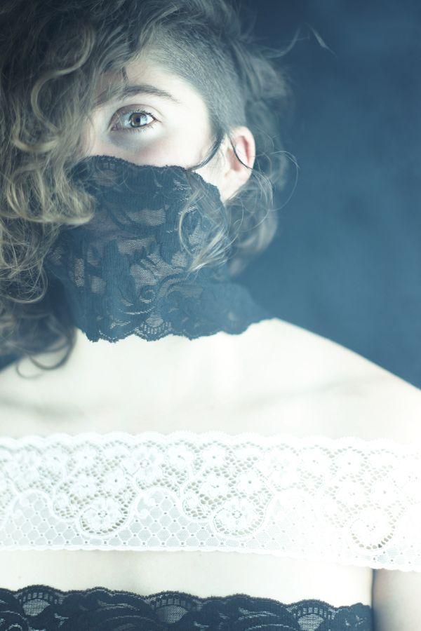 Portrait de Charlotte en studio, chez moi à Caluire-et-Cuire. La modèle avec ces cheveux mi-bouclés et mi-rasés est enroulée dans des bandes de dentelle noires et blanches. Seul son œil, énigmatique dépasse des entrelacs noirs.