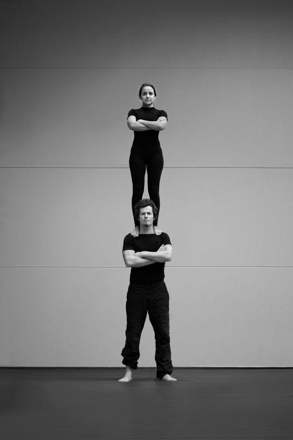 Iona et Jonas font une colonne, une figure de porté acrobatique ou AcroYoga, au gymnase d'Overground Circus à Lyon 5e. Les deux gardiens, l'un au-dessus de l'autre ont les bras croisés et arborent un air sévère.