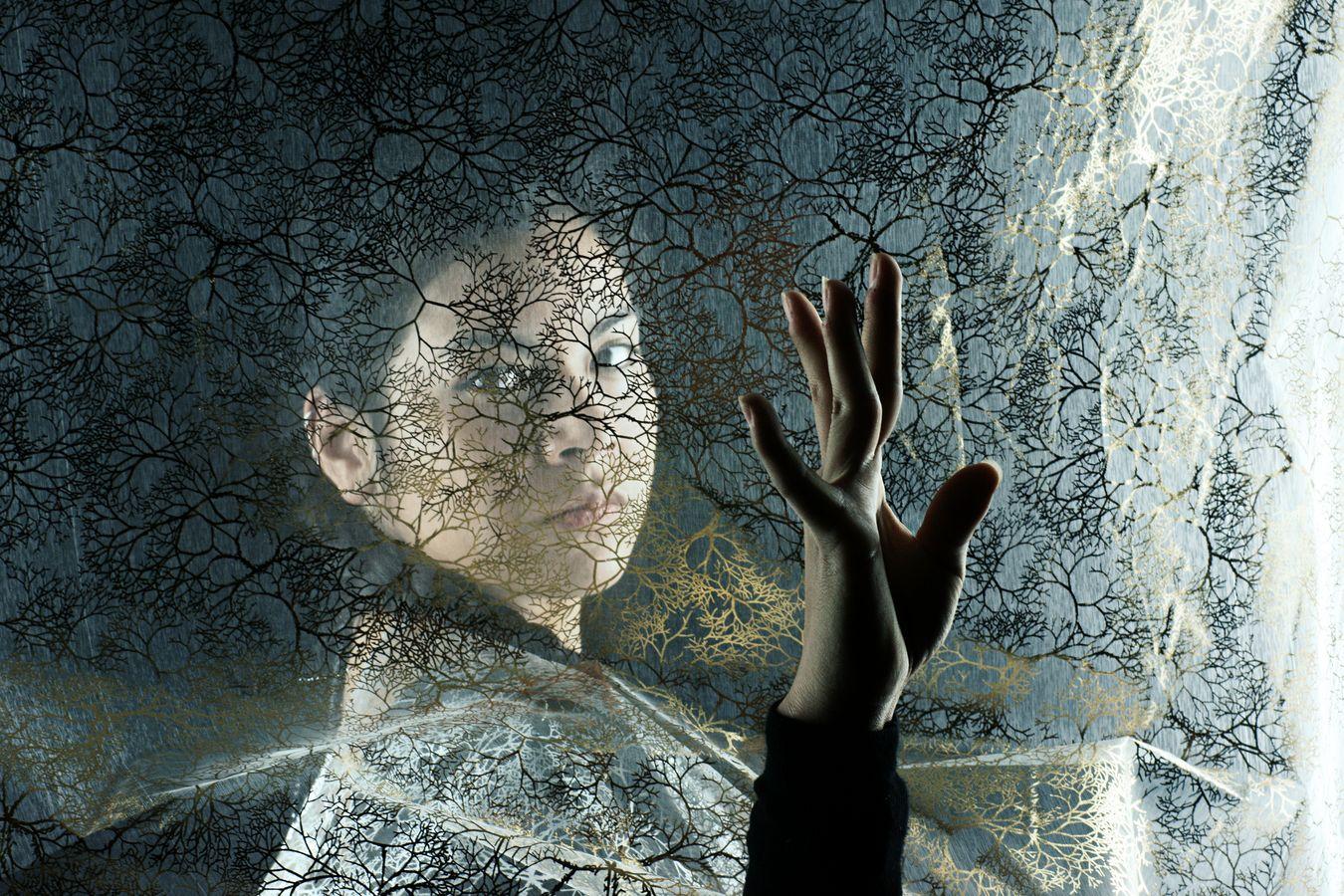Portrait d'Ana en studio derrière un tissu doré où les motifs de l'étoffe s'accordent avec ses yeux. De l'autre côté, au premier plan, sa main semble alors s'être mise à danser.