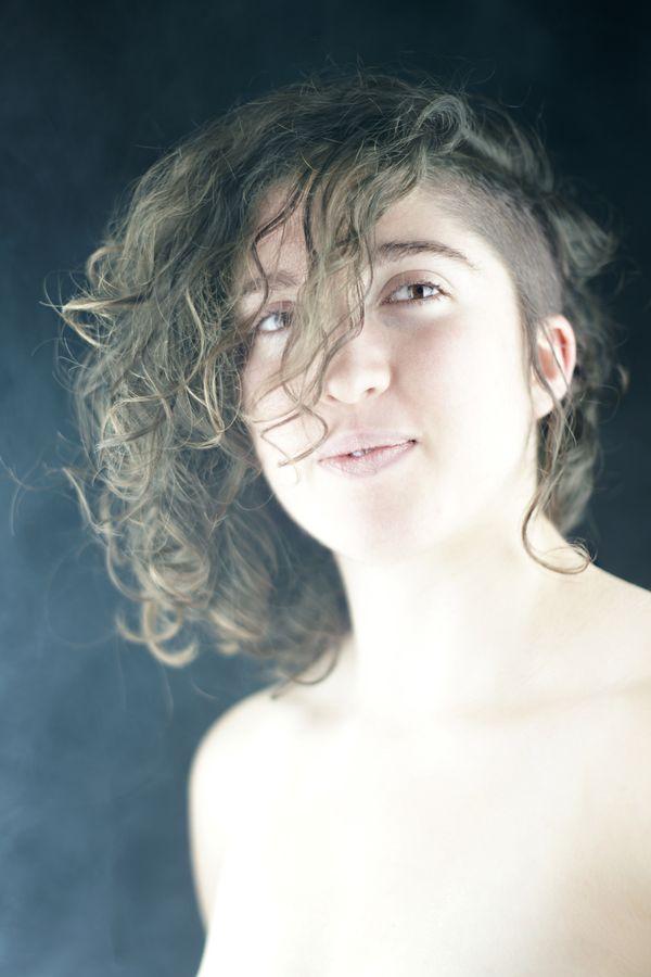 Portrait en studio de Charlotte aux cheveux mi-bouclés, mi-rasés. Une lumière douce éclaire la modèle et circassienne, alors que l'ambiance est ré-haussée par de la fumée.