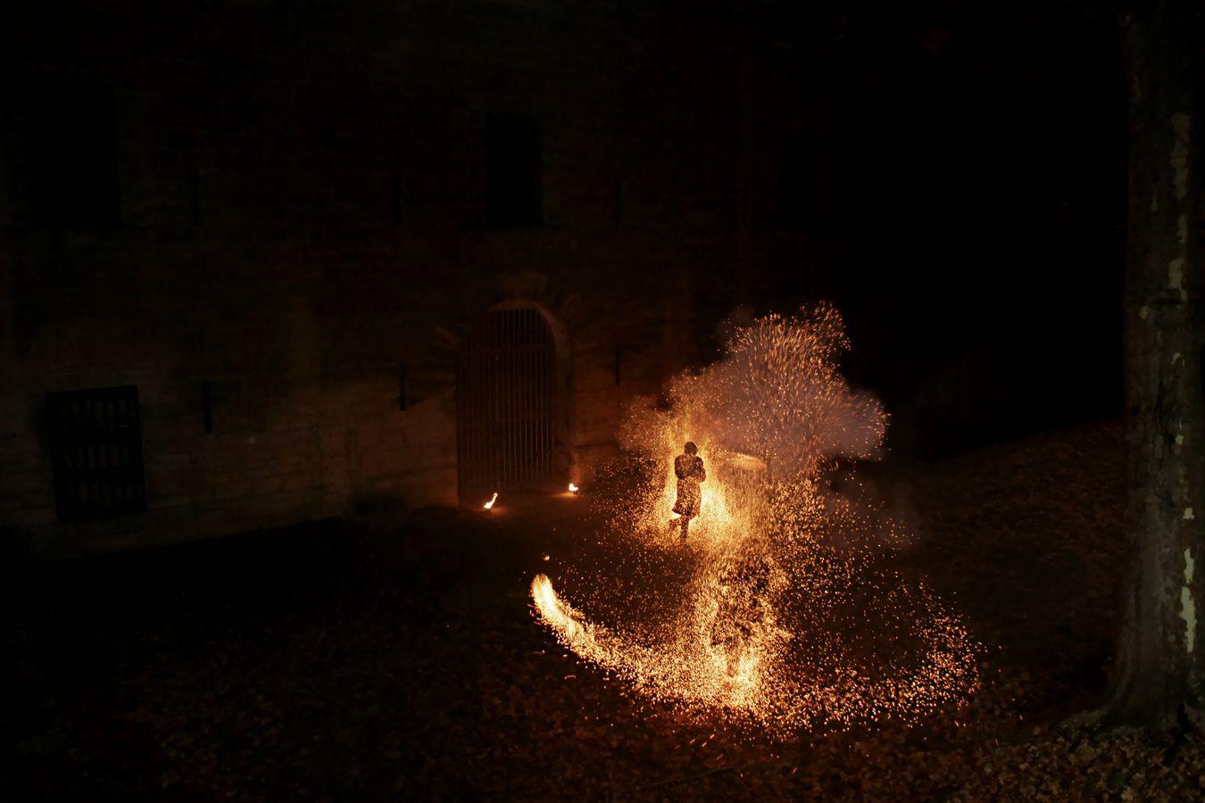 Etienne et Jean-Souleymann de la compagnie Mimétis projettent des étincelles dans tous les sens avec leur dart rope au Fort de Montessuy à Caluire-et-Cuire. Les silhouettes des deux artistes apparaissent au milieu des flammes qui semblent dessiner un œil.