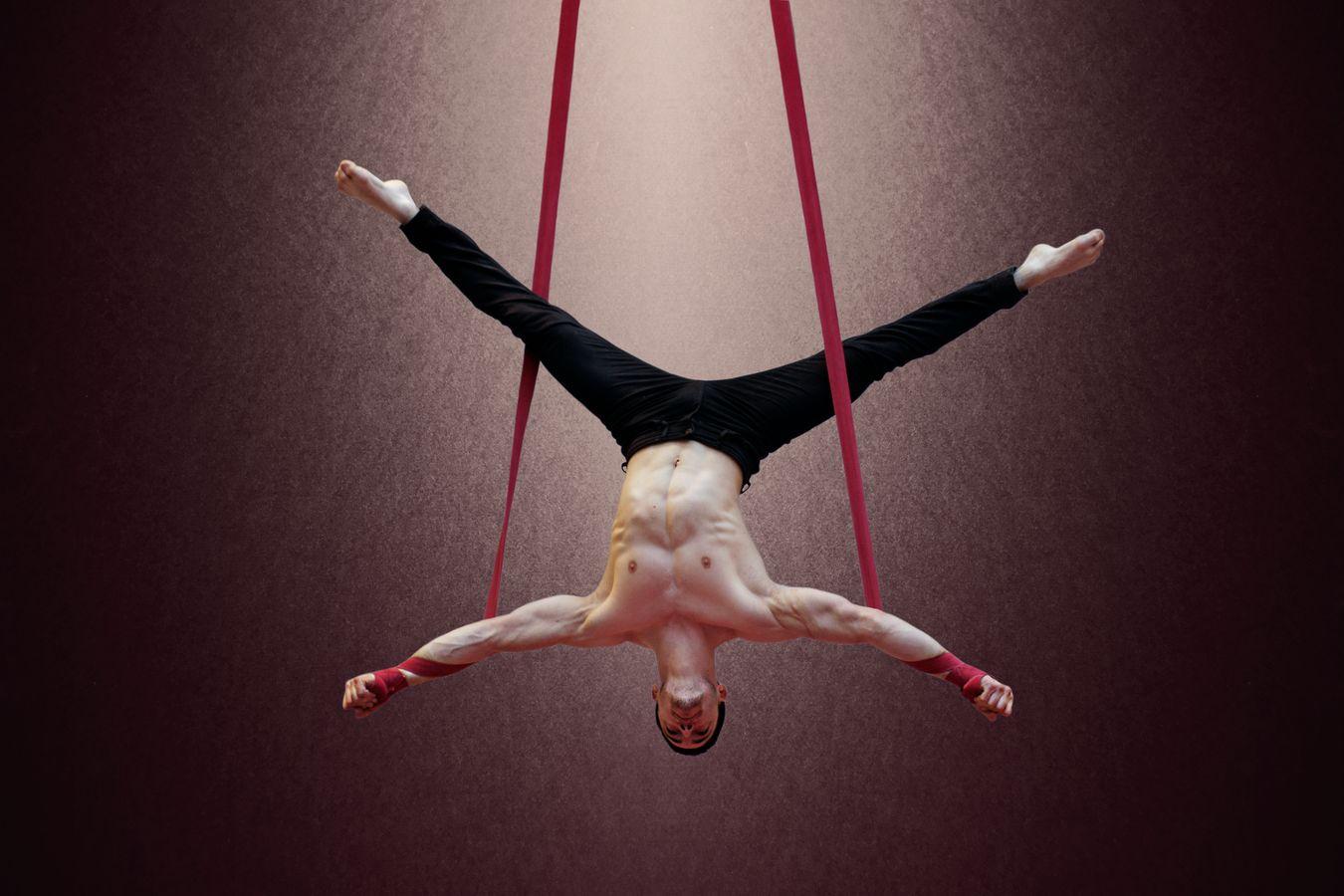 Yoann Doaré fait des sangles au gymnase d'Overground Circus à Lyon 5e. Il est torse-nu, la tête en bas et son corps dessine un X entre les sangles.