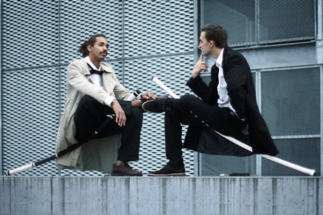 Étienne et Jean-Souleymane, de la compagnie Mimétis sont assis sur leur acrostaff au bord du bassin nautique de la Confluence de Lyon. On dirait qu'ils jouent au échecs, bien que le plateau de jeu soit énigmatiquement absent.