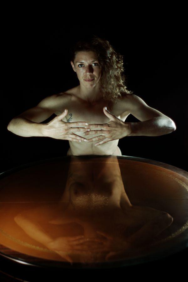 Céline est torse-nu derrière une table ronde et cache sa poitrine avec ses mains. Mais, ce geste est-il efficace vu le reflet dans le verre de la table qui donne une effet miroir ?