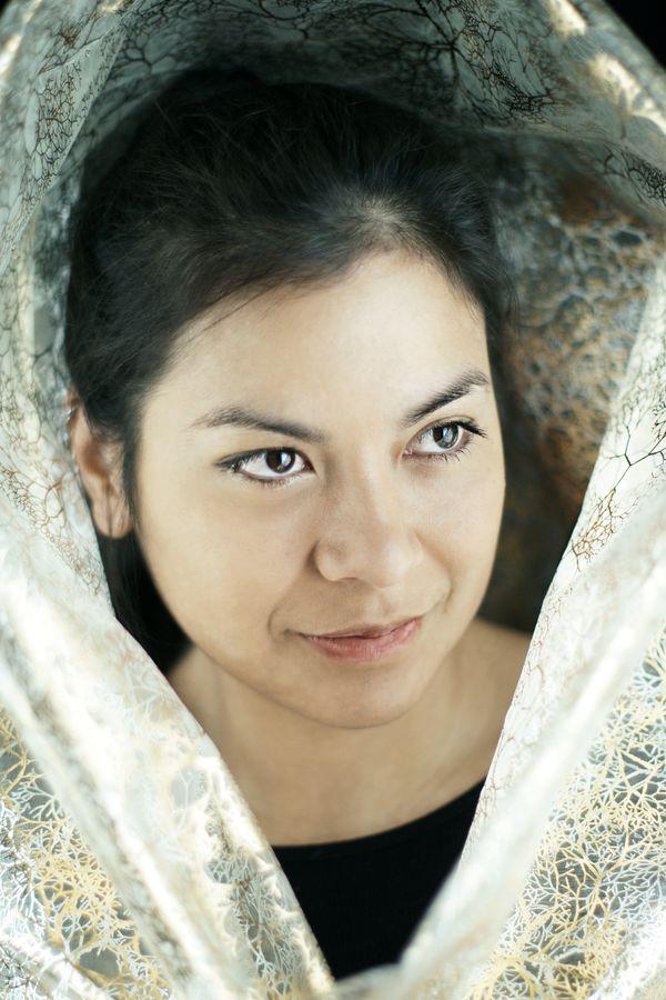 Portrait d'Ana en studio, chez-moi à Caluire-et-Cuire. Elle porte une capuche dorée qui éclaire, alors son visage. Cette modèle aux multiples visages arbore, aujourd'hui une expression enfantine.