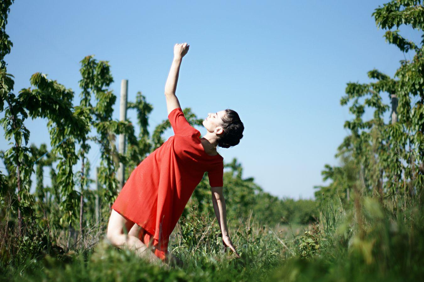 Au milieu des cerisiers de Saint-Laurent-d'Agny, Mathilde fait de la danse contemporaine en robe rouge. Son corps chute, alors en arrière comme si elle avait été renversée par le soleil.