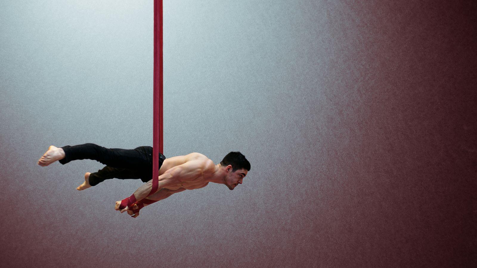 Yoann Doaré en planche aux sangles, au gymnase d'Overground circus, à Lyon 5e. Il est torse nu et tous ses muscles sont tendus pour le maintenir en l'air.