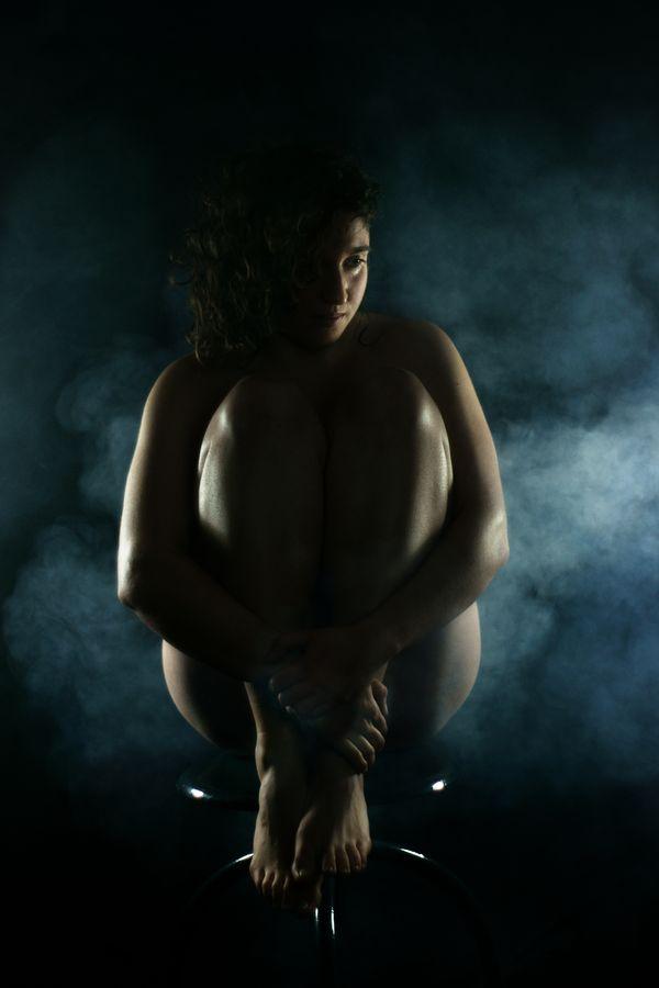 En studio à Caluire-et-Cuire, Charlotte nue, est assise sur un tabouret en métal pour un portrait dans la fumée. Elle entoure ses jambes avec ses bras.