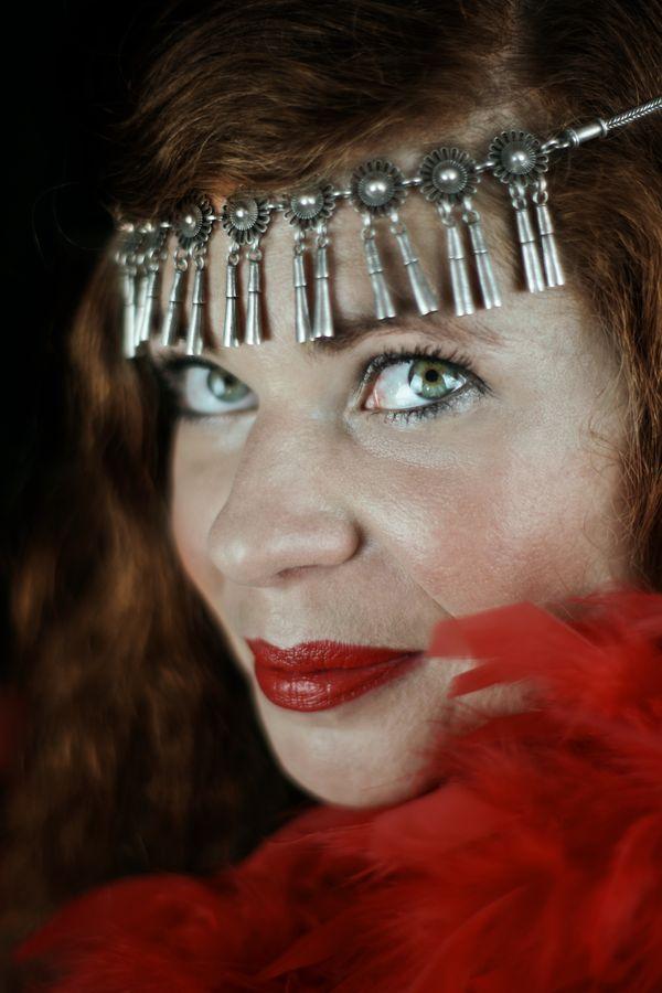 Portrait serré d'Alix Betty dans les années folles. Cheveux roux, bijoux au front et boa en plumes rouges posent une ambiance de cabaret charleston.