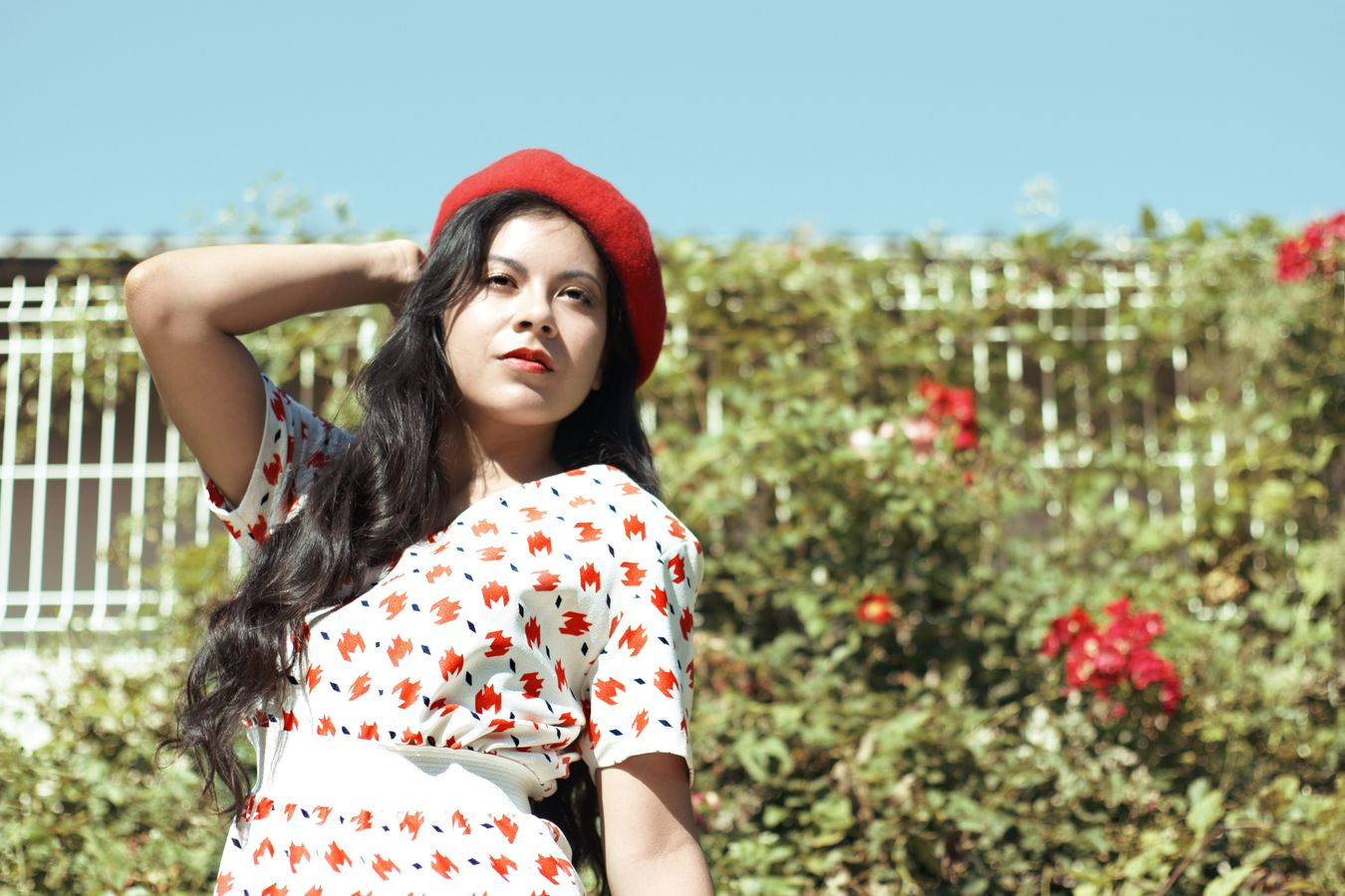 Dans les années 60, Ana attend le train sur le quai de la gare. Les motifs de sa robe vintage sont coordonnées avec les fleurs derrière elle.