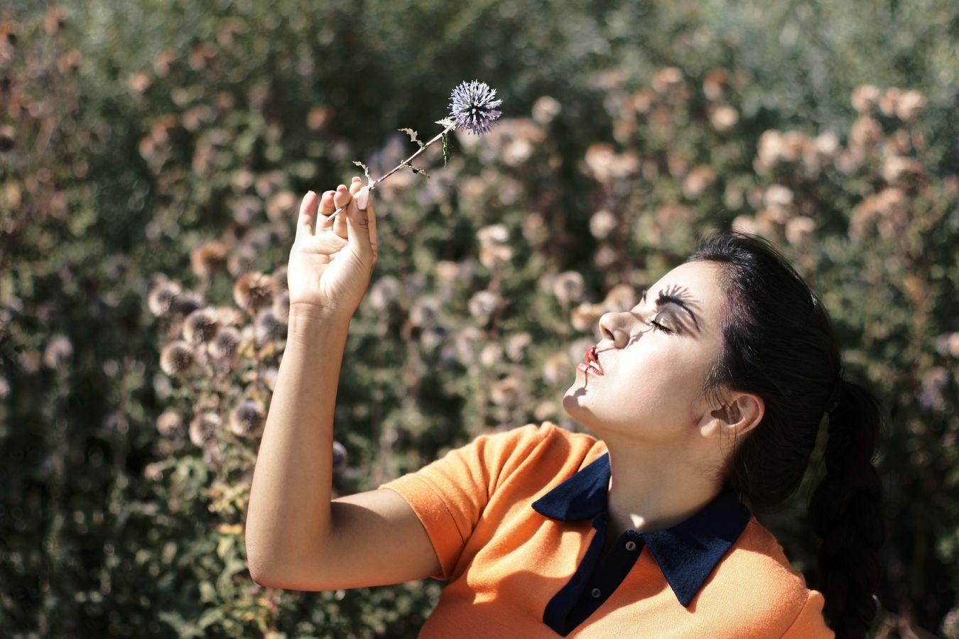 Portrait d'Ana en robe orange vintage prêtée par les Jupons de Paulette. Une fleur de chardon vient déposer son ombre sur son œil fermé.