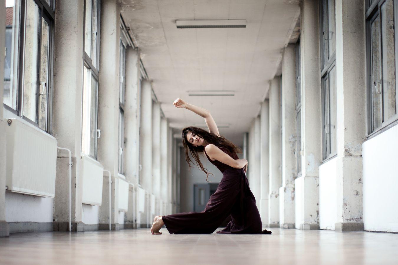 Mathilde fait de la danse contemporaine dans un couloir de l'Hôpital de la Croix-Rousse. En plein mouvement, elle vient, juste de poser un genou au sol.