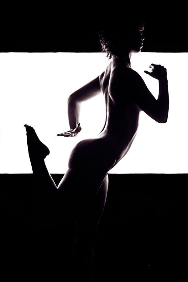 Louise, nue est en train de courir devant un fond blanc lumineux, chez moi, à Caluire-et-Cuire. Sa silhouette et sa musculature se découpent en contre-jour.